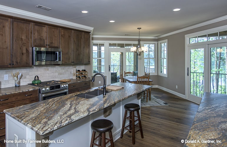 A farther view shows the natural wood cabinetry, stainless steel appliances, and subway tile backsplash.
