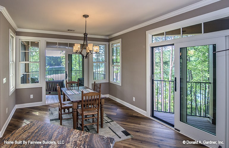 The dining area has a wooden dining set, layered rugs, and a french door that leads out to the screened porch.