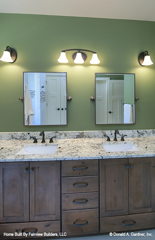 The primary bathroom features a dual sink vanity placed under the framed mirrors and glass sconces.