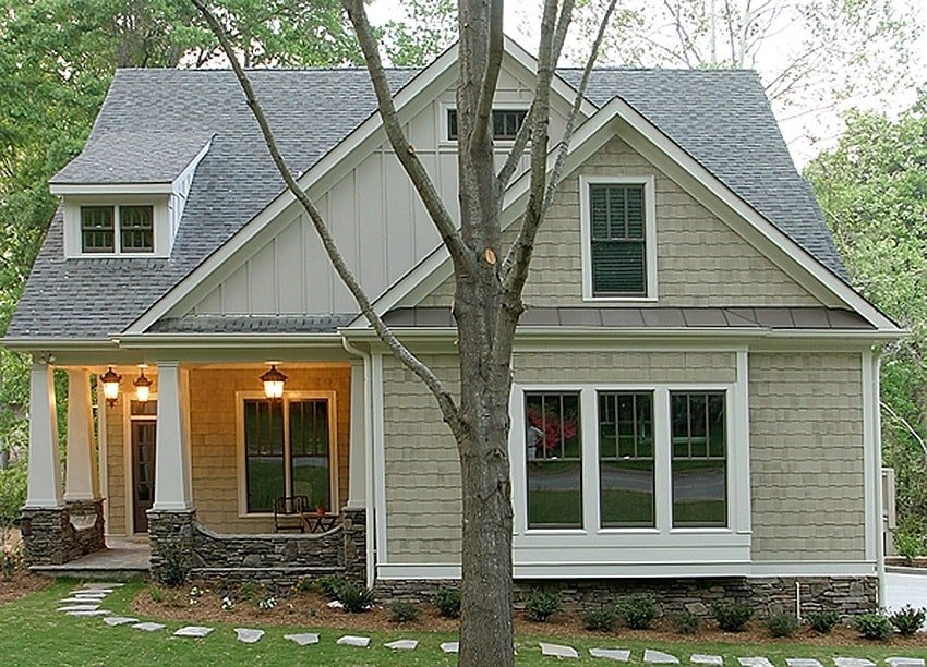 Home's front view with stone pathway and a covered porch supported by tapered columns.