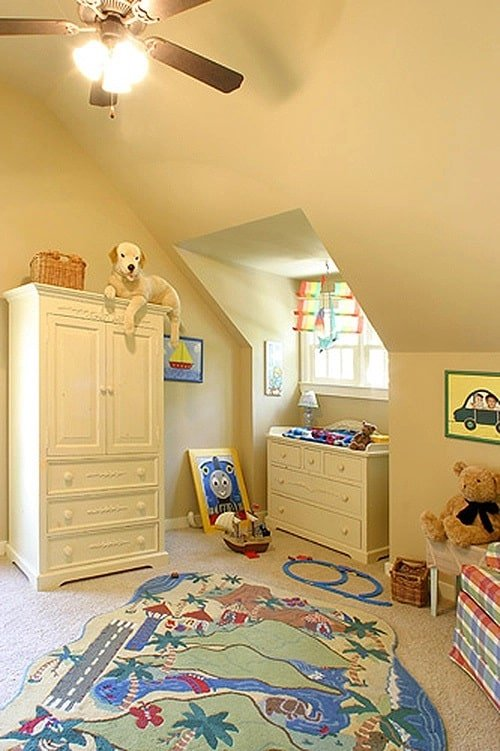 Kid's bedroom with white furnishings, a vaulted ceiling, and beige carpet flooring topped with a printed area rug.