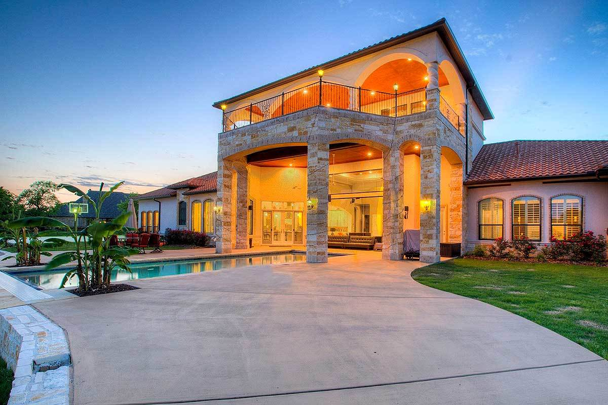 Angled rear view showing the covered balconies and a large lanai framed with gorgeous stone columns.