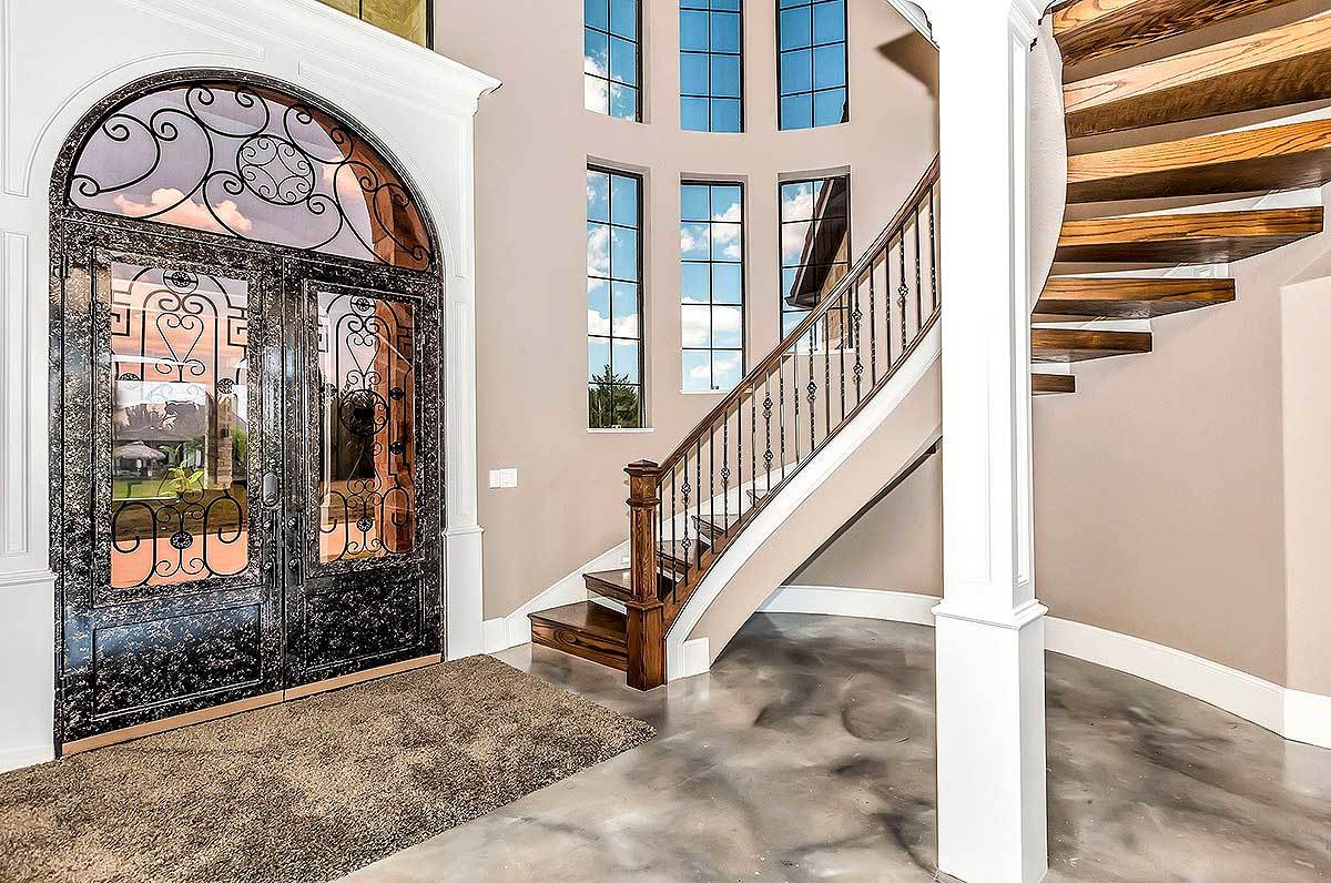 The foyer has an ornate arched front door and a spiral staircase supported by an interior column.