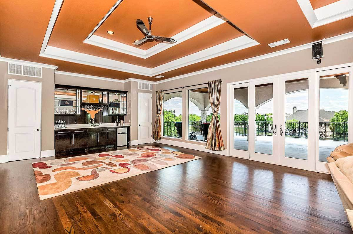 The opposite view shows a wet bar complemented with a huge printed rug