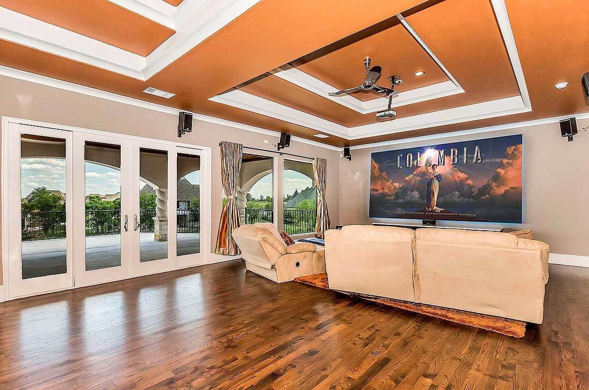 Large media room with natural hardwood flooring, an orange step ceiling, and a french door that leads out to the spacious balcony.