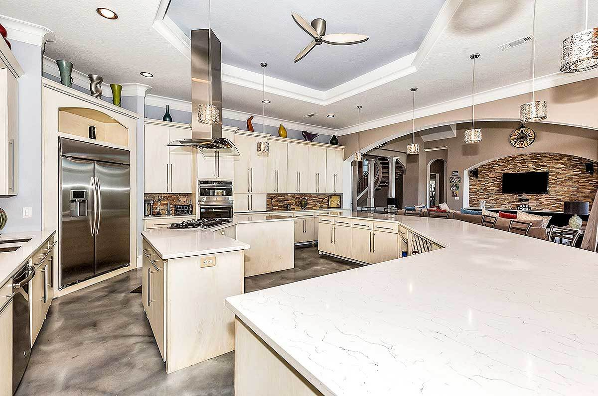 The kitchen offers sleek cabinets, stainless steel appliances, and two curved islands crowned with white marble countertops.