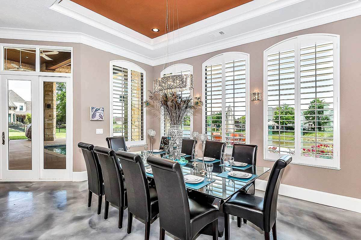 Dining area with louvered windows and black leather high back chairs surrounding the glass dining table over concrete flooring.