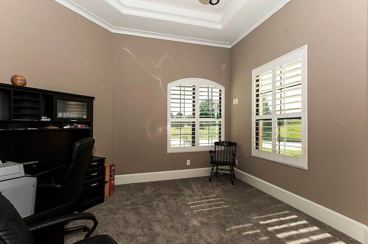 Home office with dark wood furnishings and carpet flooring that matches the brown walls.