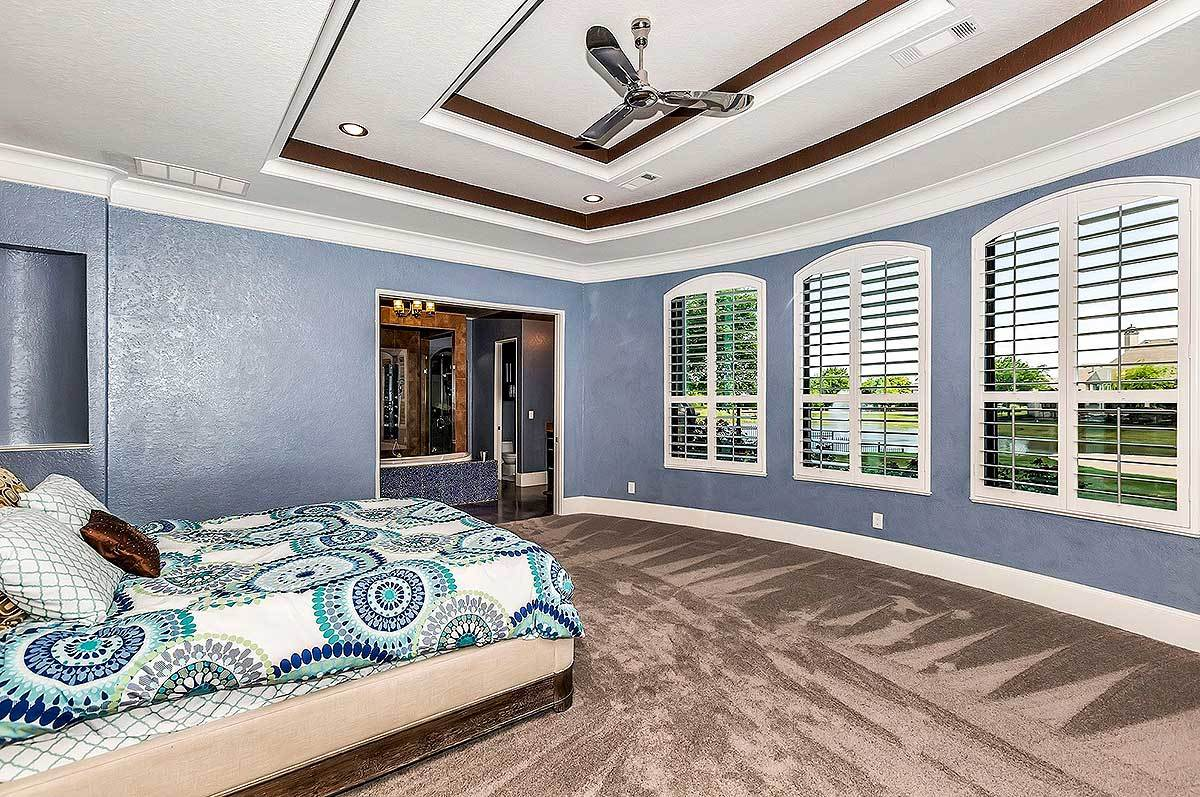 Primary bedroom with blue walls, a step ceiling, and a cozy upholstered bed that blends in with the brown carpet flooring.