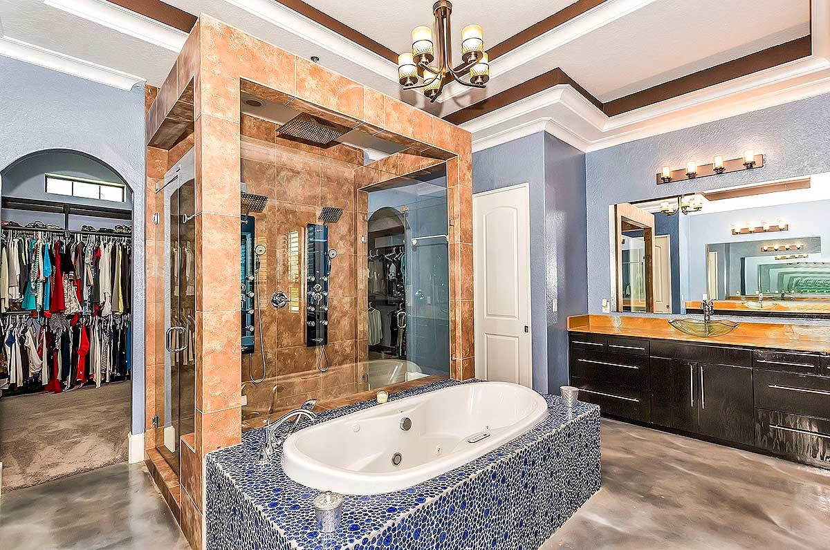 The primary bathroom is equipped with a vessel sink vanity and a drop-in bathtub situated in front of the walk-in shower.