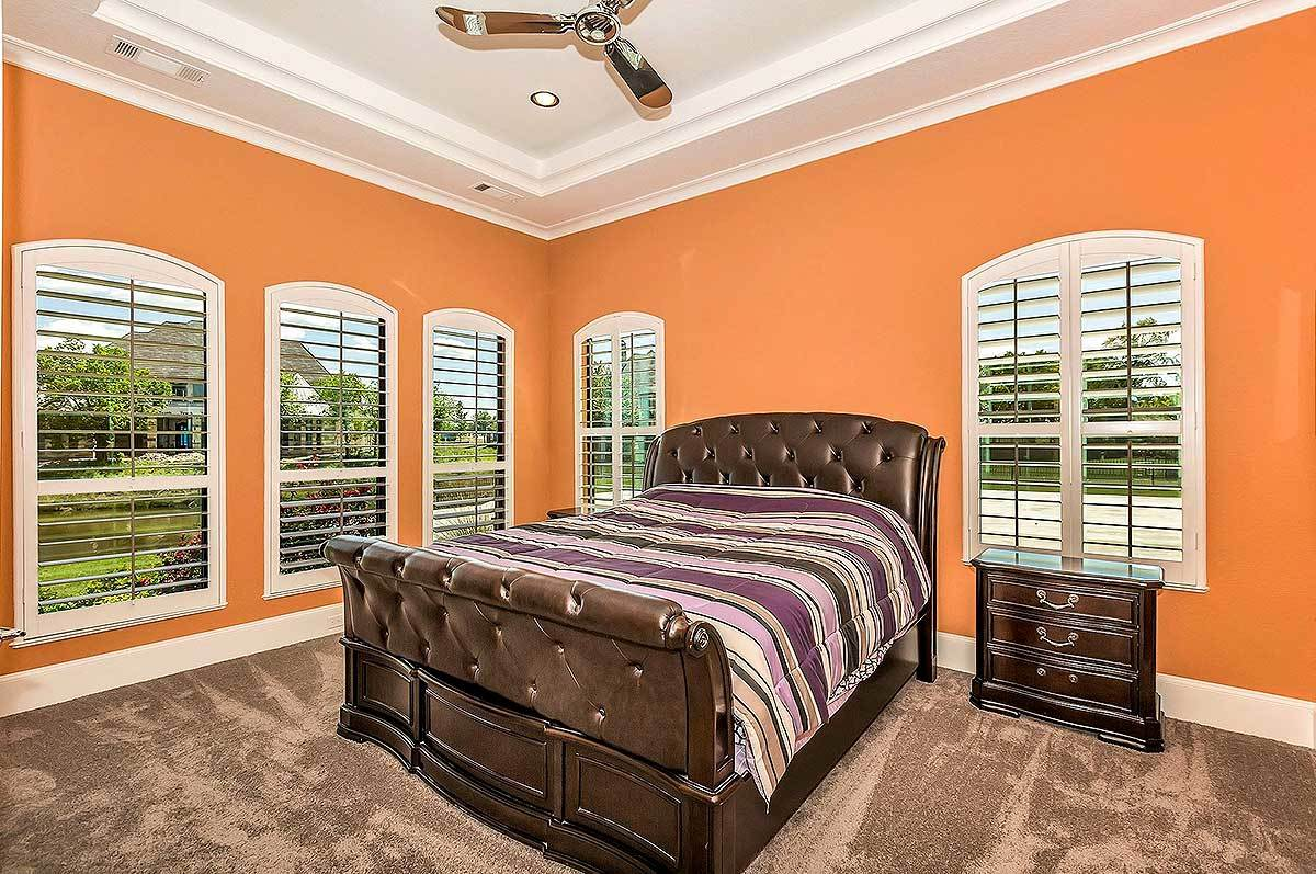 This bedroom has a leather tufted bed, a wooden nightstand, and arched windows that invite plenty of natural light in.