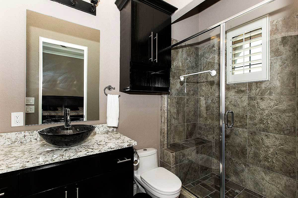 Bathroom with a walk-in shower, sink vanity, and a toilet sitting under the floating black cabinet.