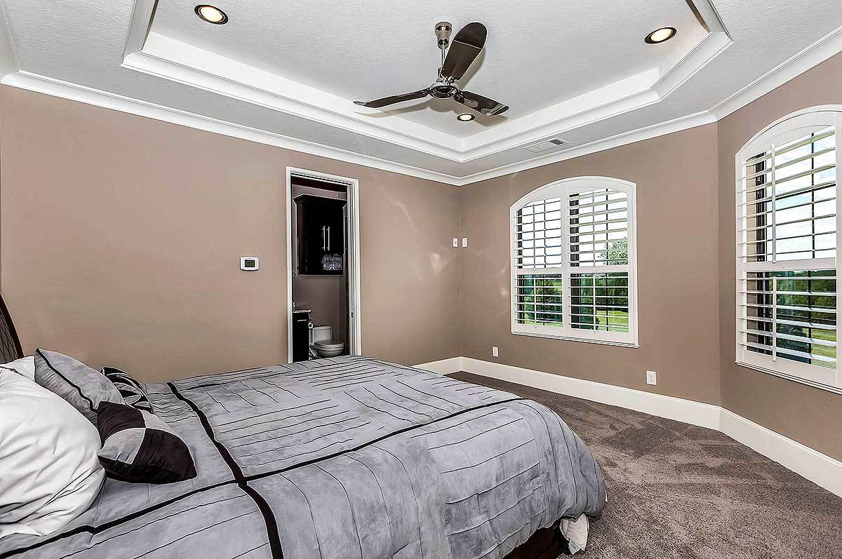 Another bedroom with brown carpet flooring and walls along with a tray ceiling mounted with a sleek fan and recessed lights.