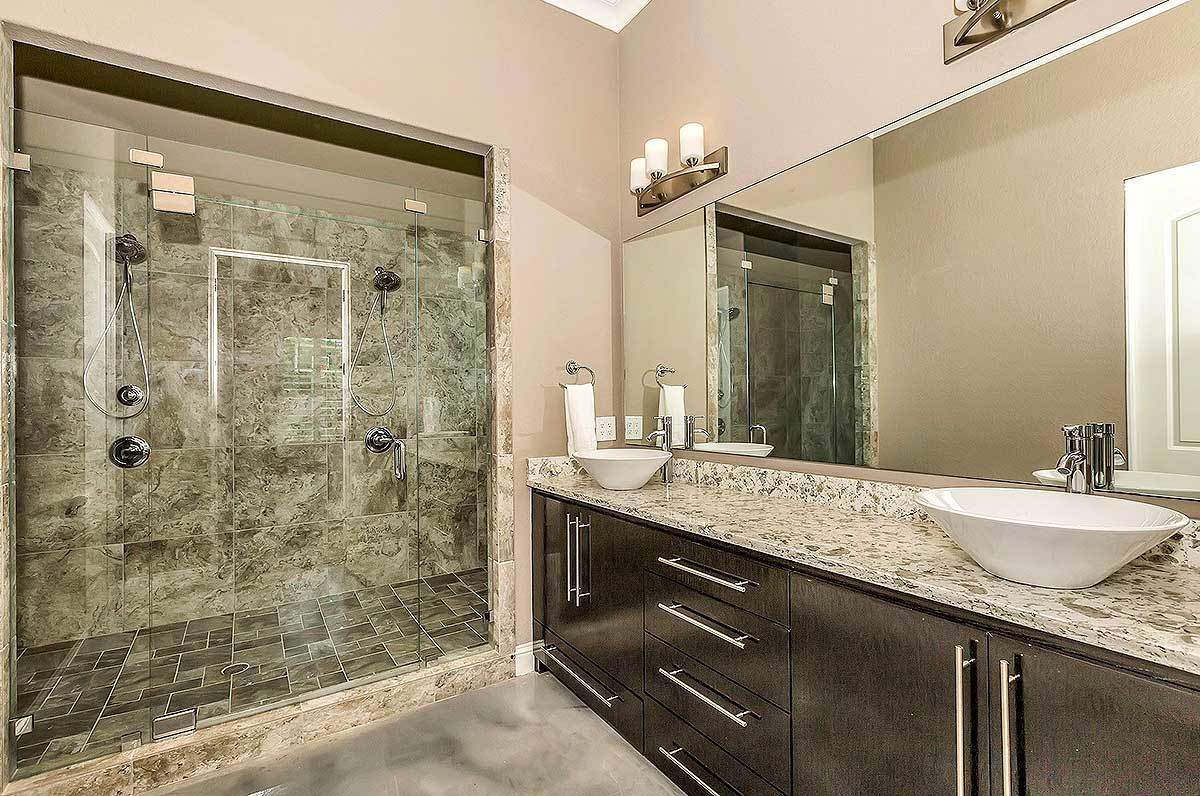 This bathroom offers a spacious walk-in shower and a huge dark wood vanity topped with white vessel sinks and an elegant granite countertop.