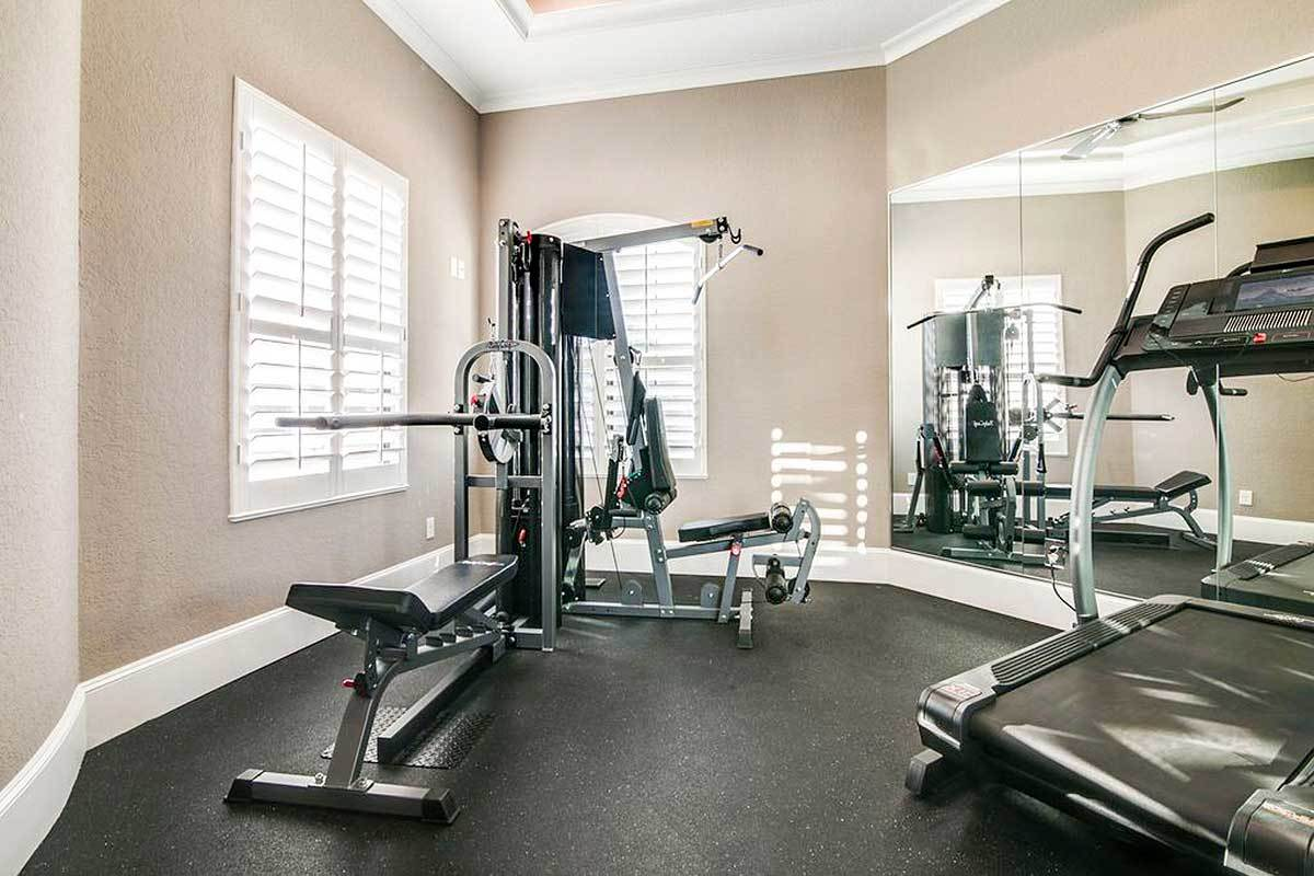 Various exercise equipment along with frameless mirrors fill the home's gym.
