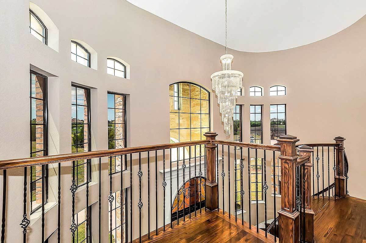Second-floor balcony with ornate wrought iron railings and a beaded cascading chandelier that hangs from the white oval ceiling.