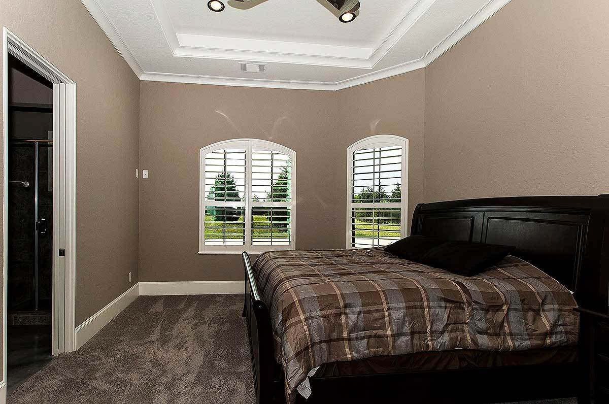 This bedroom has arched windows and a dark wood bed covered in a brown checkered duvet.