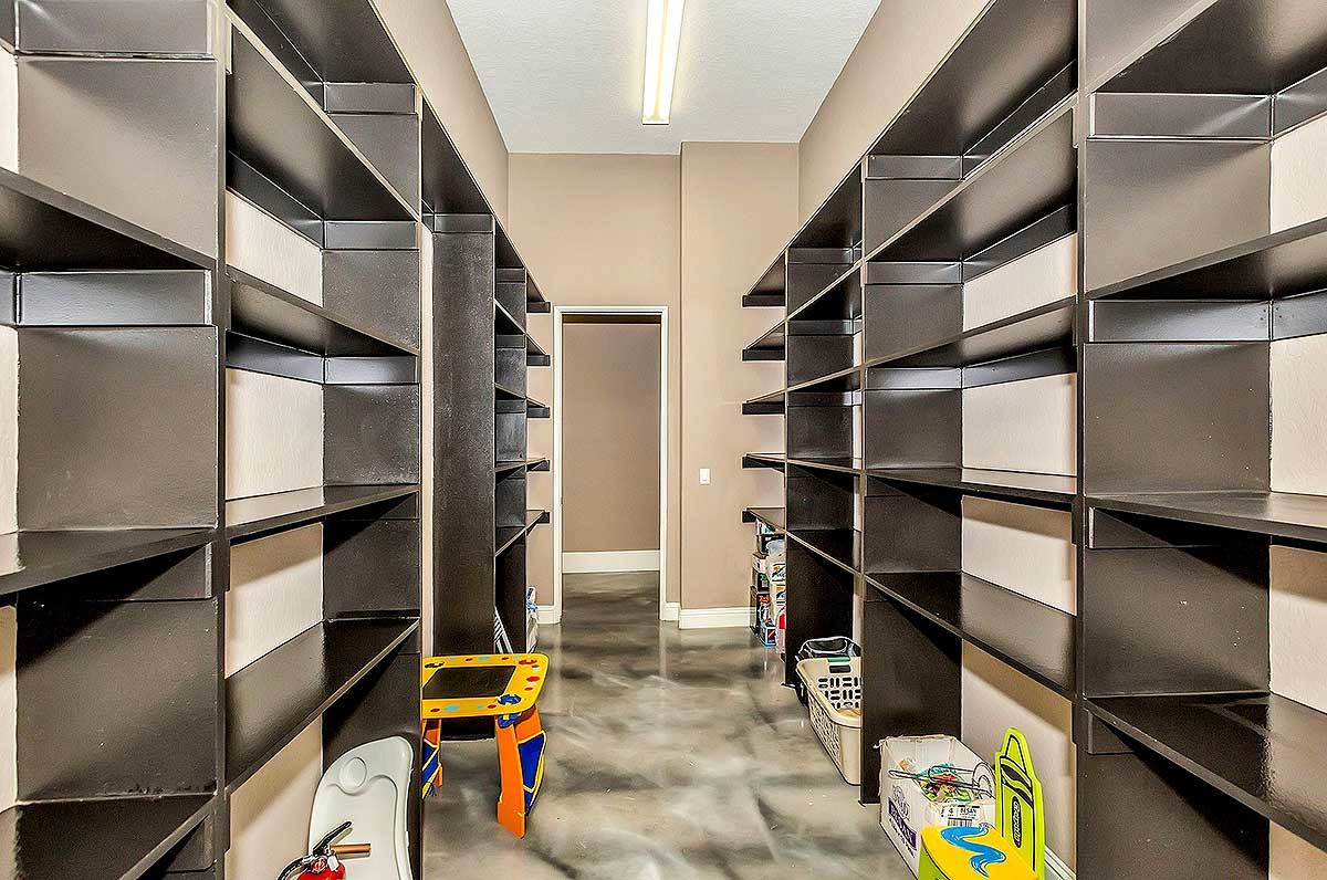 A large pantry filled with tons of dark wood shelvings that are fixed against the beige walls.