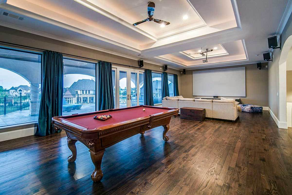 Spacious recreation room with a media area and a billiard table.