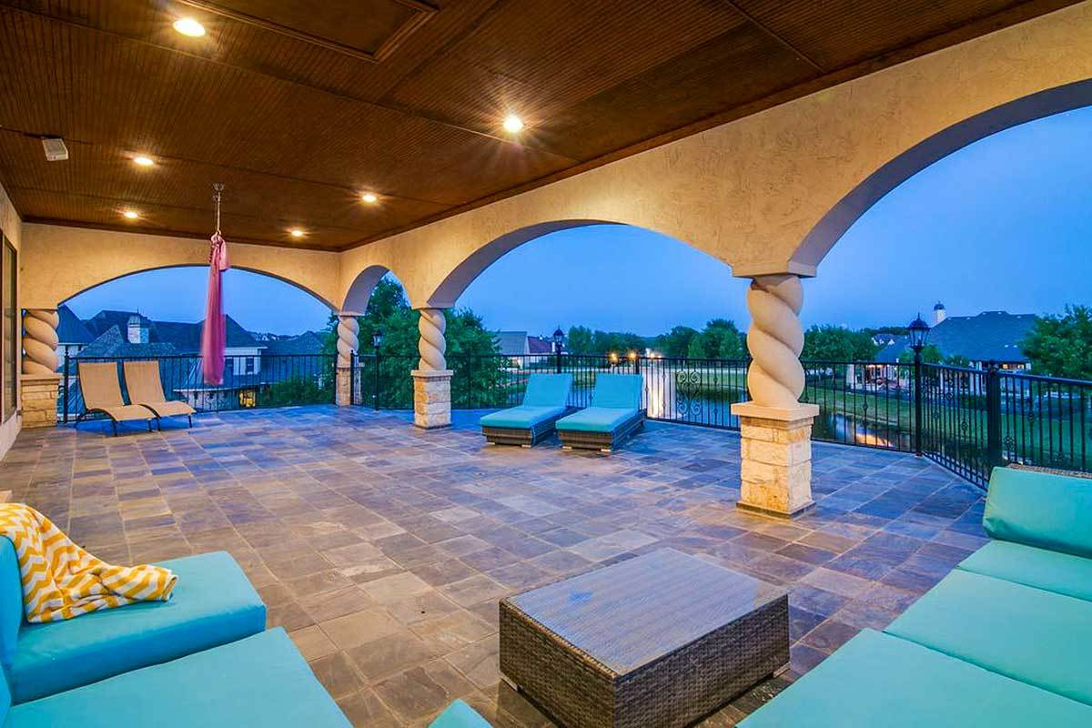 An expansive balcony offering cozy loungers and a blue L-shaped sectional paired with a wicker coffee table.