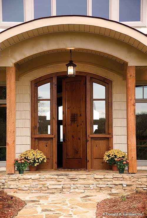 Home entry featuring an arched front door lit by a warm glass sconce hanging from a barrel-vaulted ceiling.