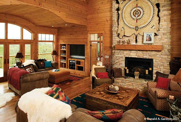 The living room offers multiple sitting areas and a stone fireplace lined with a wooden mantel.