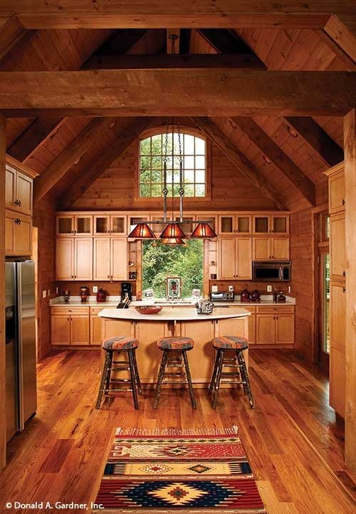 The kitchen has light wood cabinets, a tasseled tribal rug, and a breakfast bar lined with round bar stools and glass pendants.