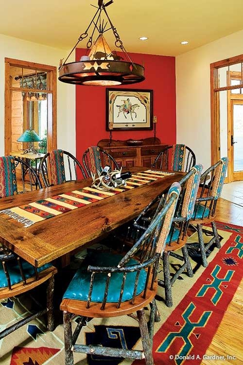 Dining area with a round chandelier, blue cushioned chairs, and a rectangular dining table topped with a striped runner.