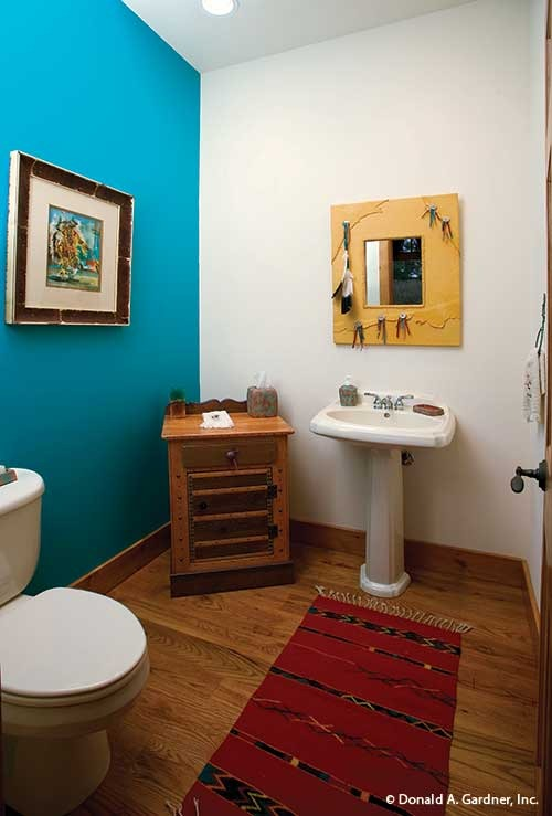 This bathroom offers a toilet, a wooden cabinet, a pedestal sink under the framed mirror, and a red tasseled runner that lays on the hardwood flooring.