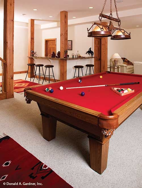 Recreation room with a wrapped around wet bar and a billiard table under the vintage pendant light.