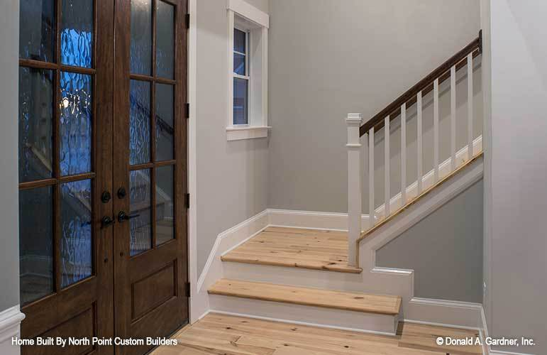 The foyer has a french front door and a traditional staircase fixed against the gray walls.