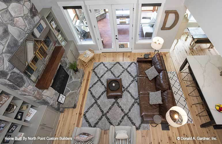 Top view of the living room showing the light hardwood flooring topped by patterned rugs.