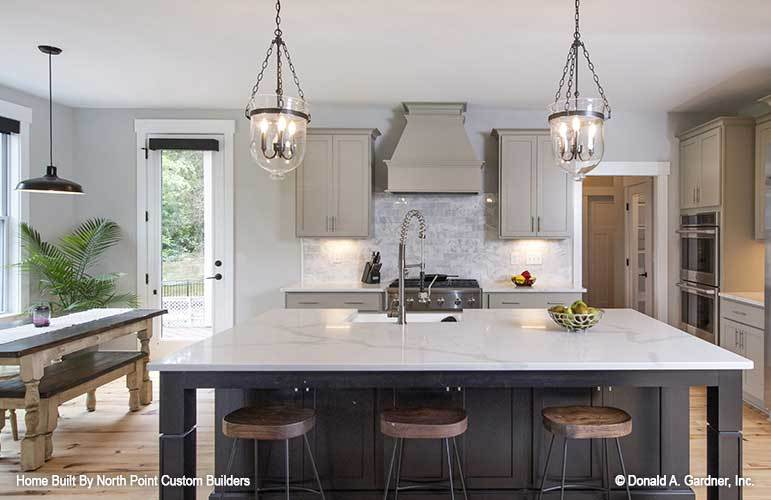 A pair of glass pendants along with round bar stools complement the marble top island.