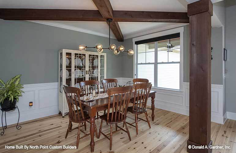 The formal dining room offers a white display cabinet and a wooden dining set illuminated by a contemporary chandelier.