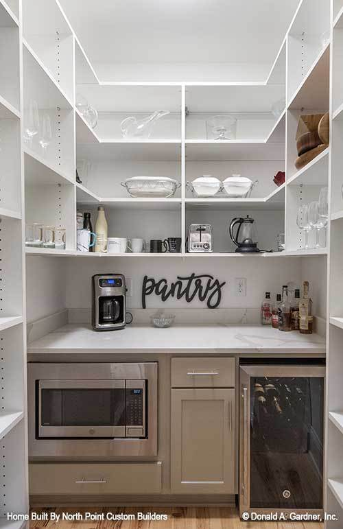 Butler's pantry with white shelvings, marble countertop, wall oven, and a beverage fridge.