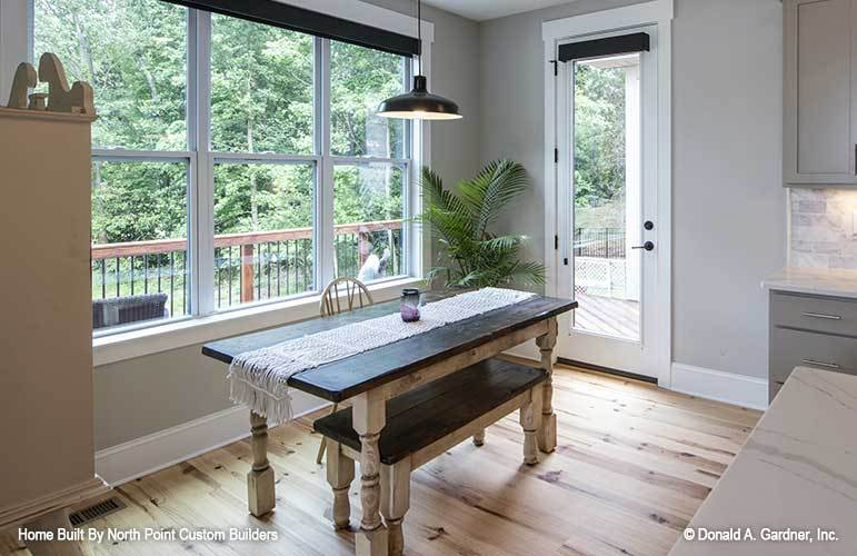 The breakfast nook has a glass dome pendant, round back chair, a wooden bench, and a rectangular table topped with a tasseled runner.