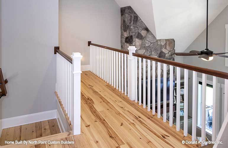 Balcony loft with natural hardwood flooring and white wooden railings.