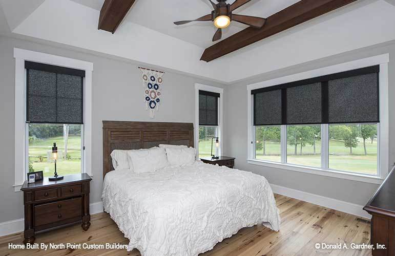 The primary bedroom has light gray walls, wide plank flooring, and a coved ceiling lined with dark wood beams.