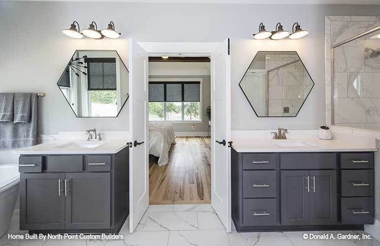 Primary bathroom featuring two sink vanities placed under the hexagonal mirrors and wall sconces.