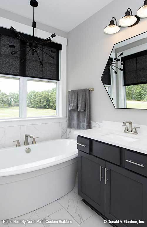 There's also a freestanding tub on the side well-lit by a black sputnik chandelier.