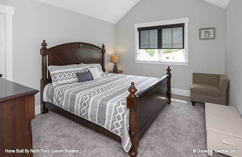 This bedroom has wooden furnishings, a cathedral ceiling, and gray carpet flooring.