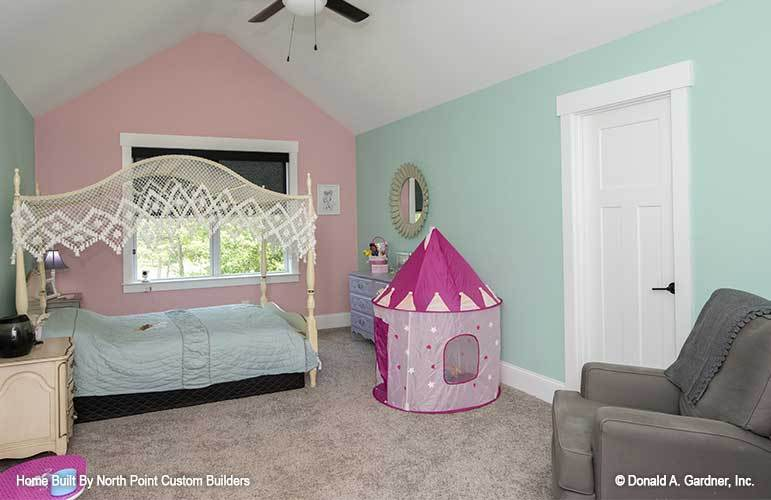 Kid's bedroom with multi-colored pastel walls, a lovely canopy bed, gray armchair, and distressed drawers.