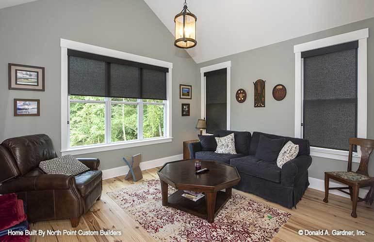 The sitting room is furnished with a brown leather armchair, a skirted couch, a wooden chair, and an octagonal coffee table over a red patterned rug.