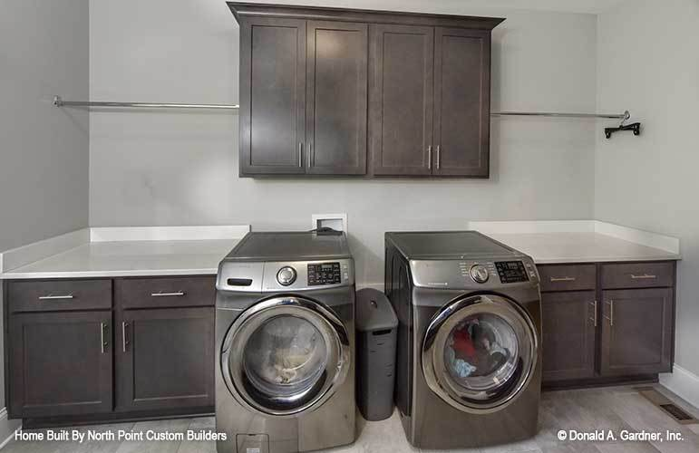 The utility room is equipped with stainless steel front load appliances, quartz countertop, and wooden cabinets.