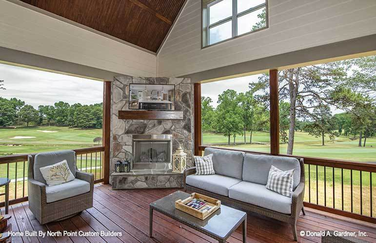 Screened porch with a high vaulted ceiling, wicker furnishings, and a corner fireplace with a TV on top.