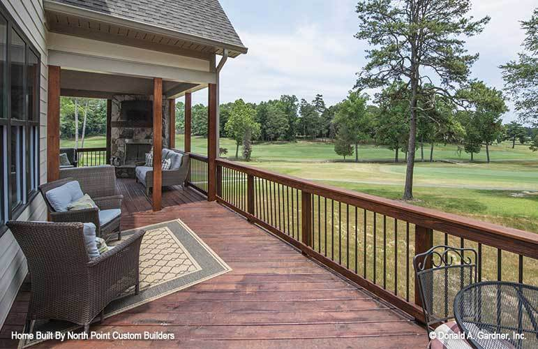 Rear deck with wicker armchairs, a patterned area rug, and a serene expansive view.