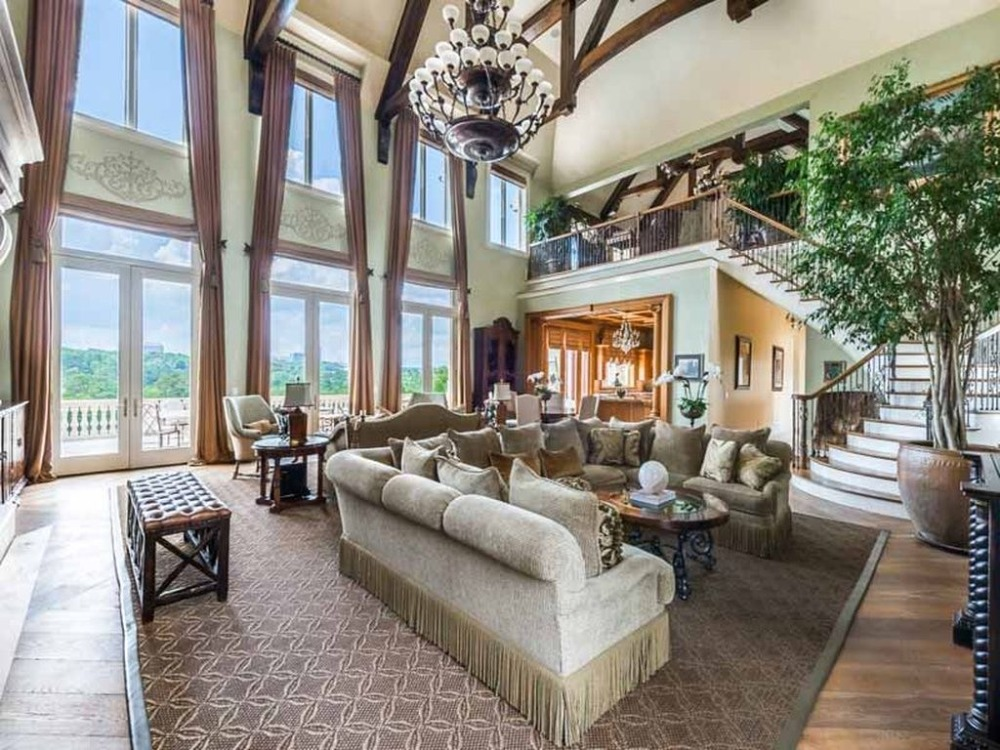 Another look at the living space with a large fireplace, glass doors and windows and a high ceiling. Images courtesy of Toptenrealestatedeals.com.