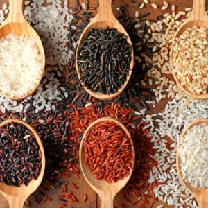 The different types of rice on a wooden table with wooden spoons.