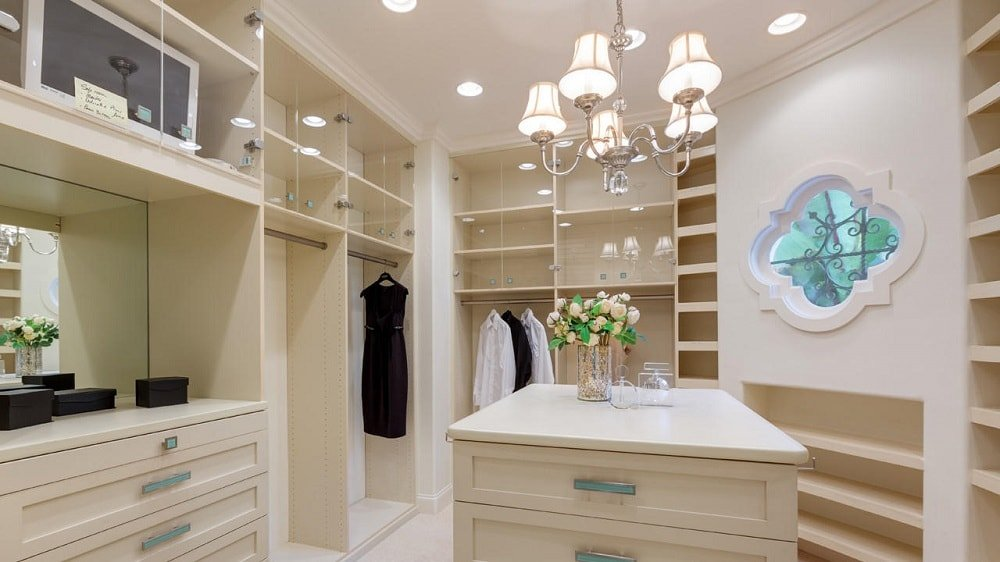 The primary bedroom has a large walk-in closet with beige cabinetry and built-in shelves on the walls. These are then complemented by a small chandelier over the island. Image courtesy of Toptenrealestatedeals.com.