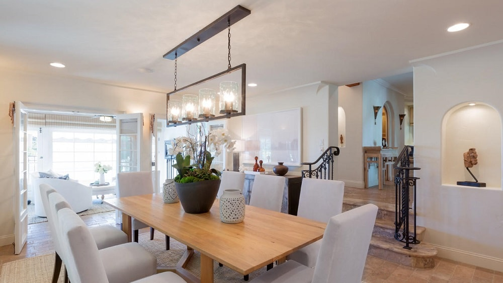 The dining room has a large rectangular wooden dining table surrounded by beige cushioned chairs and topped with decorative lighting that contrasts the ceiling. Image courtesy of Toptenrealestatedeals.com.